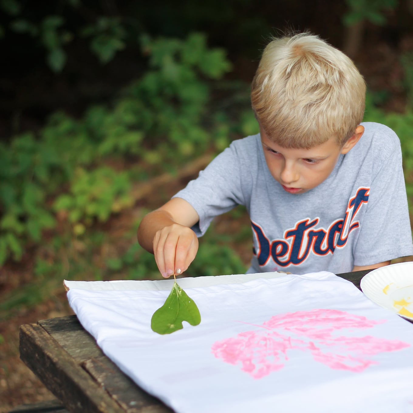 Child Stamping Leaves on T-Shirt