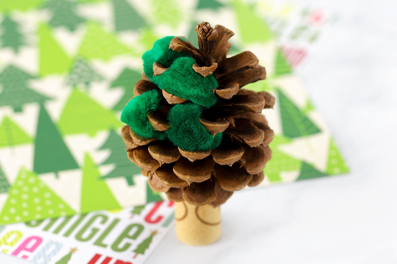 Putting Green Pompoms into the Pine Cone