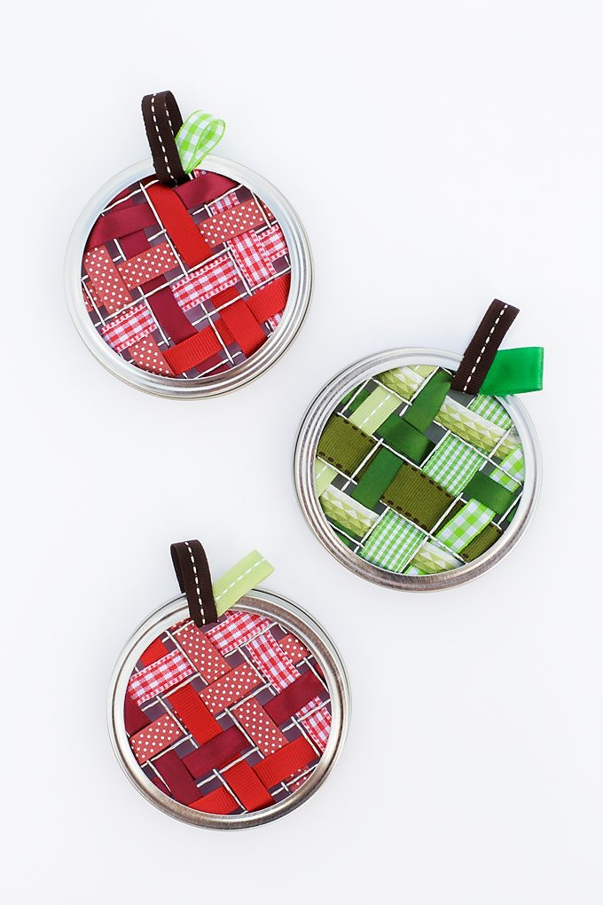 Celebrate apple season with colorful Scrap Ribbon Apple Suncatchers. They are made with mason jar frogs, rings, bits of scrap ribbon, and glue!