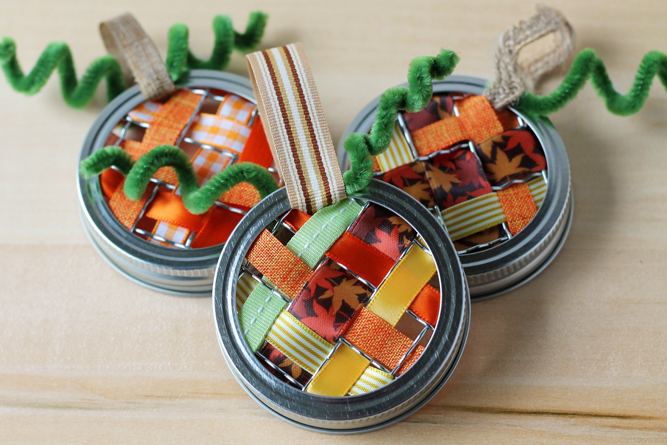 Just in time for fall, learn how to make vibrant pumpkin suncatchers with scraps of woven ribbon and mason jar lids. This weaving craft is perfect for kids!