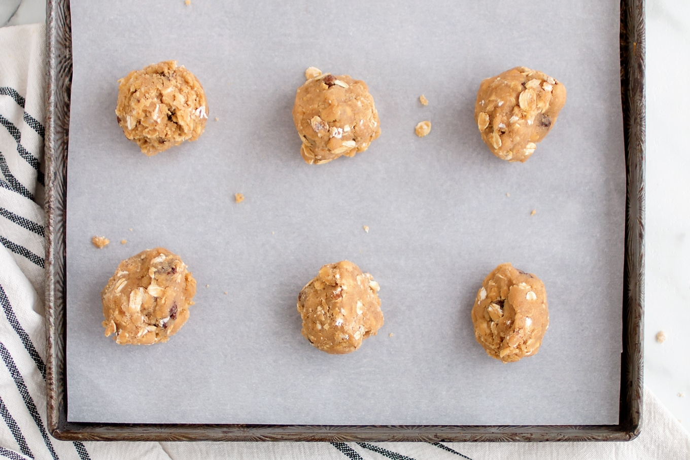 Oatmeal Raisin Cookie Dough on Parchment-Lined Pan